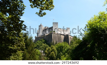 View of the Festung Hohensalzburg framed by lush green trees on summer day in Salzburg, Austria, Europe - stock photo