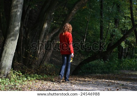 View of the girl from a back. The girl walks in autumn park. - stock photo