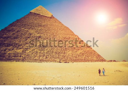 View of the Giza Pyramids, the tourists near them. Fantastic evening glowing by sunlight.  Egypt. Cairo. Filtered image:cross processed effect.  - stock photo