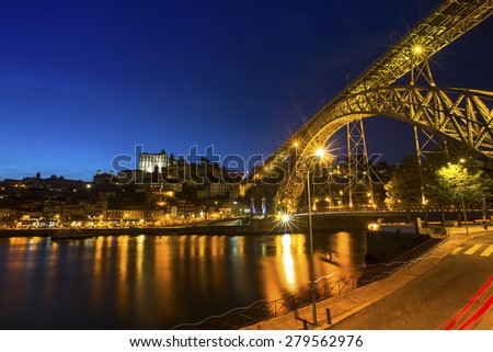 View of the historic city of Porto, Portugal with the Dom Luiz I bridge at night time. - stock photo