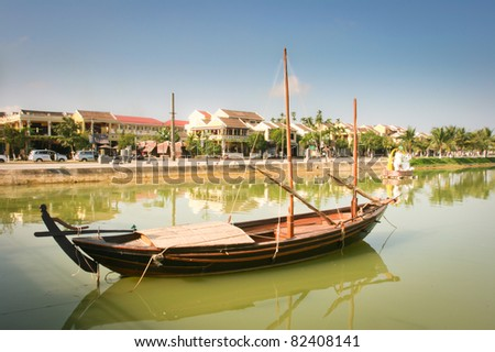 View of the Hoi An old town from the Thu Bon River. Boat in the foreground. Vietnam - stock photo