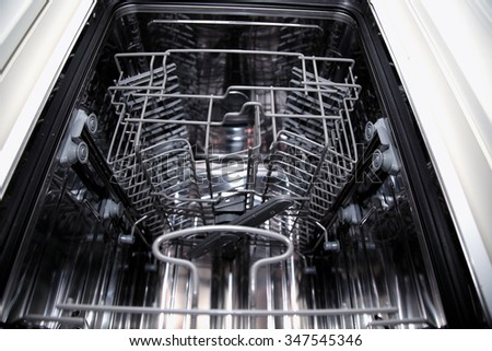 View of the interior of an empty opened dishwasher - stock photo