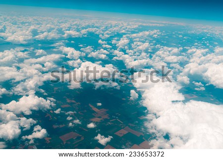 View of the land, fields, and clouds from above
