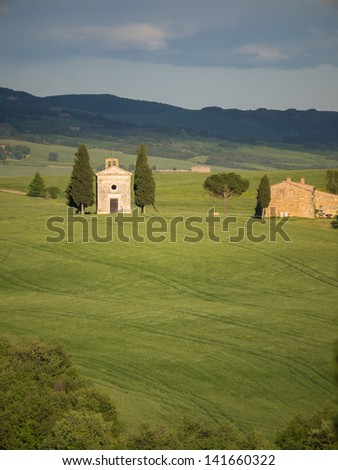 View of the little chapel of Capella di Vitaleta in the Tuscan landscape of the Val d'Orcia as the sun starts to set - stock photo