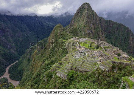 View of the Lost Incan City of Machu Picchu and Huayna Picchu mountain from Machu Picchu mountain .Low clouds .Cusco Region,Sacred Valley, Peru - stock photo