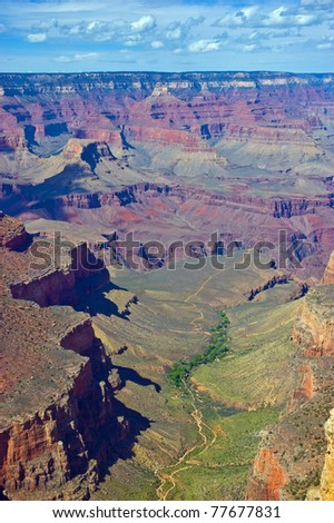 View of the majestic Grand Canyon taken at the south rim and showing trails and small buildings near green trees along a stream, in vertical format - stock photo