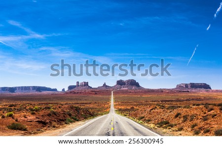 View of the Monument Valley and the highway 163 in Utah during a beautiful summer day. Vivid blue sky against the colorful desert and the rocks. The road is vanishing in the Monument Valley.