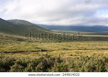 View of the Ngorongoro Crater  Panorama of Ngorongoro Crater with sunny blue sky with few clouds and gravel road.  - stock photo