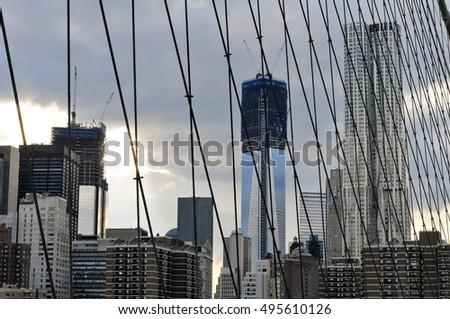 View of the NYC Skyline from the Brooklyn Bridge in the summer.