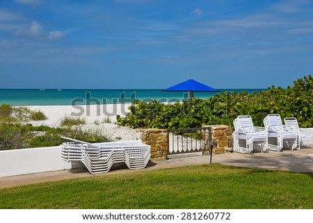 View of the Ocean and White Sandy Beach from the lawn of a Resort with private access to the Beach  - stock photo