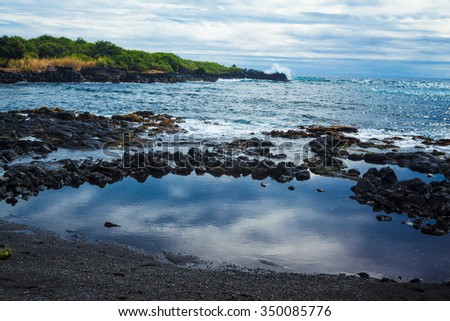 View of the ocean from the black sand beach in Hawaii - stock photo
