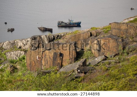 view of the old rocks, stones and ship in the kola gulf near Murmansk - stock photo