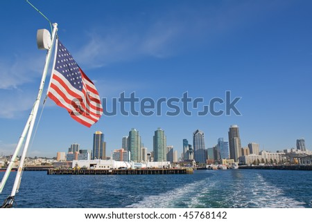 View of the port and skyline of San Diego, California, from the taffrail of a whale-watching vessel with the American flag, bright blue sky and white clouds - stock photo
