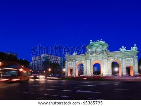View of the Puerta de Alcal? in Madrid, Spain with lights of oncoming traffic.  It was commissioned by King Carlos III, with construction beginning in 1778.