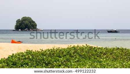 View of the Rengis island from the beach of Tioman in Malaysia with ships at sea on a cloudy day
