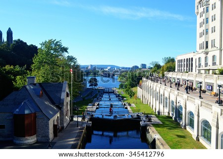 View of the rideau canal in Ottawa, Canada, with the locks open anda hotel on the right side, in bright sunshine. - stock photo