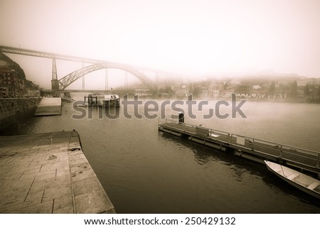 View of the River Douro and the metal bridge of Don Luis in Porto. The fog. Toned. - stock photo