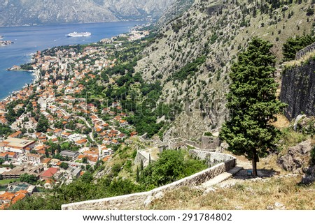 View of the roofs of the houses and the marina with a fortress wall in the old town of Kotor, Montenegro - stock photo