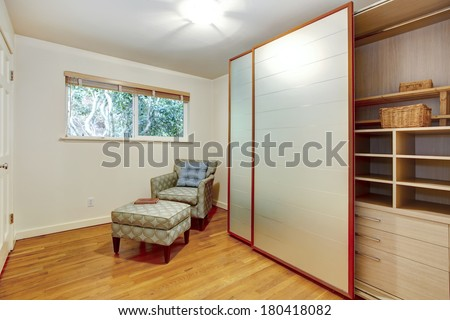 View of the room corner with chair and open slide doors wardrobe cabinet with shelves, drawers and basket - stock photo