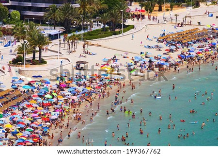 View of the sandy beach full of people sunbathers and swimmers in the hot afternoon sun (Spain, Benidorm) - stock photo