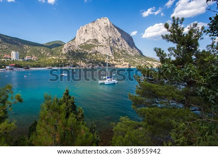 View of the sea bay in the village Novyi Svit on the background of mount Falcon in the Crimea in the summer - stock photo
