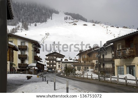 View of the settlement of Livigno and mountain-skiing routes in the Italian Alps. - stock photo