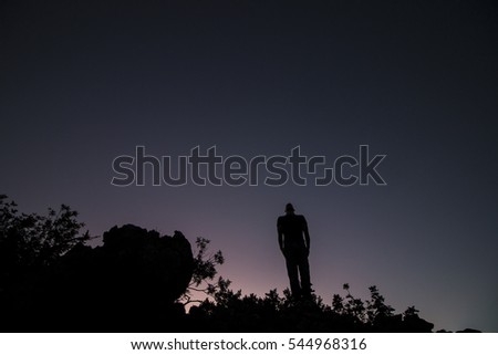View of the silhouette of a man on top of a hill.