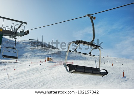 View of the ski slopes and chair lifts on winter sunny day - stock photo
