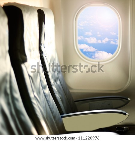 View of the sky and clouds with sunlight from the airplane window,empty seats. - stock photo