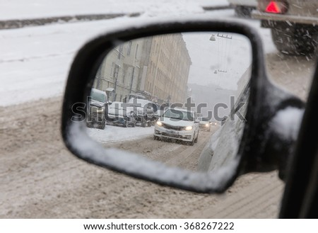view of the snow-covered street during a snowfall in a European city in the side rear view mirror - stock photo