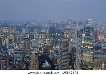 View of the sprawling metropolis of Tokyo, Japan at dusk with illuminated tall modern skyscrapers and buildings - stock photo
