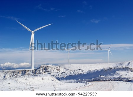 View of the three windmills to generate electricity on a snowy mountain - stock photo