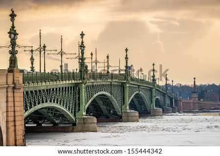 View of the Trinity Bridge in St. Petersburg over the frozen Neva River in during the afternoon. - stock photo