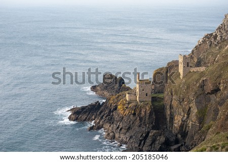 View of the two ruined engine houses of the Crown Mines , Botallack, Cornwall perched on a cliff overlooking the undersea shaft extending under the ocean floor in search of tin, now a heritage site - stock photo