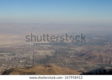 View of The valley from the top of the San Jacinto Mountains in California with a very dense and thick smog layer - stock photo