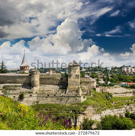 View of the walls and towers of the ancient Kamenetz-Podolsk fortress from the grassy slopes in the foreground. National Historical and Architectural Reserve Kamenetz-Podolsk, Ukraine.  - stock photo