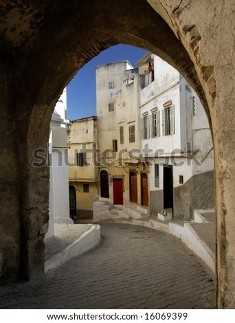 View of the winding hill street in Tangier, Morocco, North Africa. Shot through a gate in the city wall. - stock photo