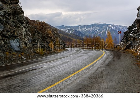 View of the winding mountain road through the pass,  part of the mountain serpentine, in autumn cloudy weather with fog