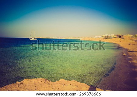 View of the yacht on Red Sea and the rocky coast. Egypt.  Filtered image:cross processed vintage effect.  - stock photo