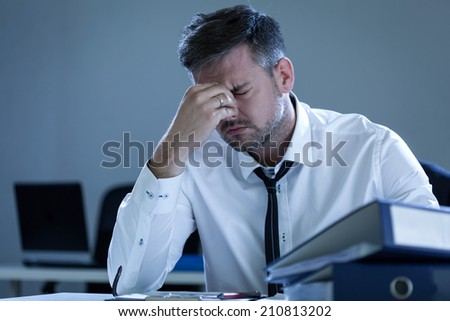 View of tired businessman in the office - stock photo