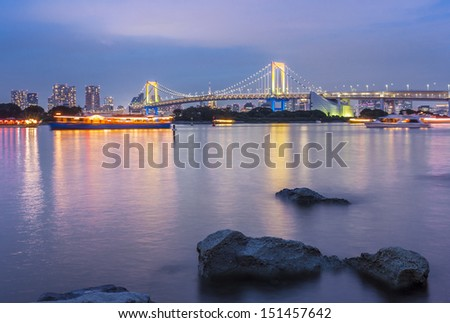 View of Tokyo skyline and Rainbow bridge at twilight - stock photo
