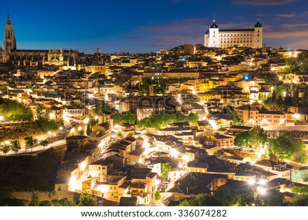 View of Toledo, Spain including Alcazar and the cathedral at dusk.