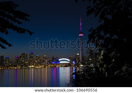 View of Toronto skyline in the dusk hour, beautiful light colours reflected on the lake water - stock photo