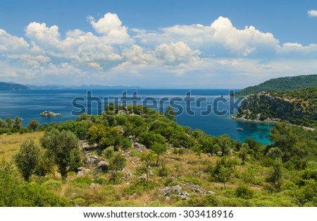 view of trees and plants covered hill on sunny day against blue sky with Aegean sea at background, Amos bay, Marmaris, Turkey