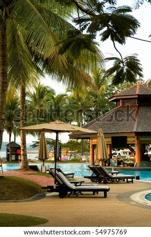 View of tropical resort swimming pool scene in evening - stock photo