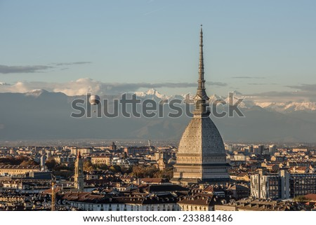 View of Turin, Italy at sunset with the Mole Antonelliana and the snow capped peaks of the Alps on the background. - stock photo