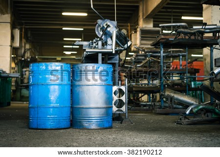 view of two blue industrial barrels with the paint worn off,  laid upright on the floor of an industrial hall, with shelves full of metal pieces of exhaust pipes and metal manufacturing  - stock photo