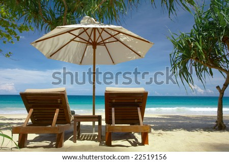 view of two chairs and white umbrella on the beach. - stock photo