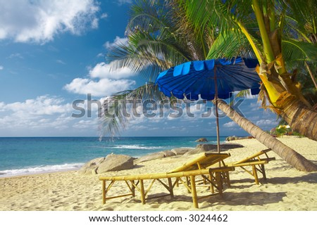 view of two exotic bamboo chase lounges and blue umbrella - stock photo