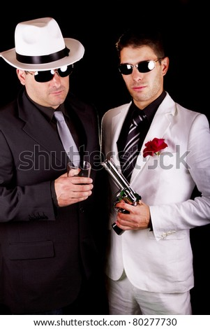 View of two gangster males holding a gun on a black background.